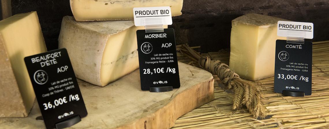 Des cartes de prix accrocheuses de la taille d'une carte de crédit à côté de savoureux produits fromagers